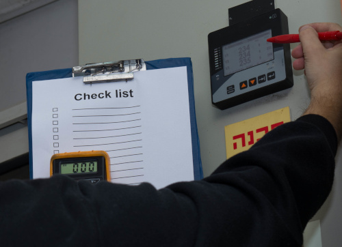 A worker holds up a checklist on a clipboard in front of an electrical panel.