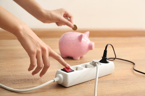 Hands turn off a surge protector while putting a coin in a piggy bank. Saving energy means saving money!